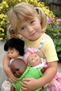Three year old girl playing with Asian, African American and Caucasian dolls MR